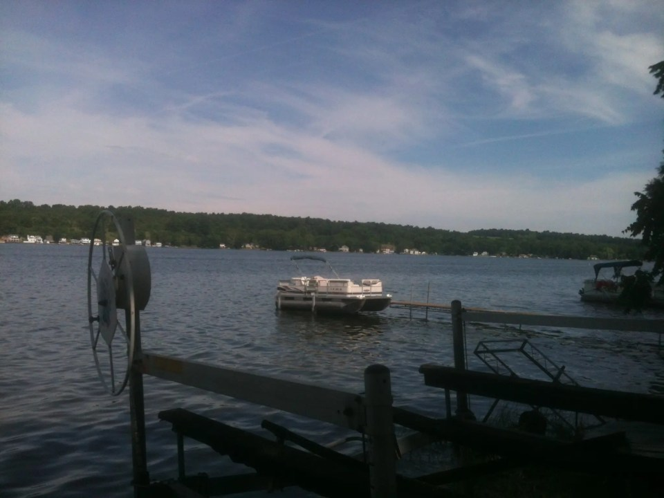 shows a boat on a small lake in one of upstate New York towns
