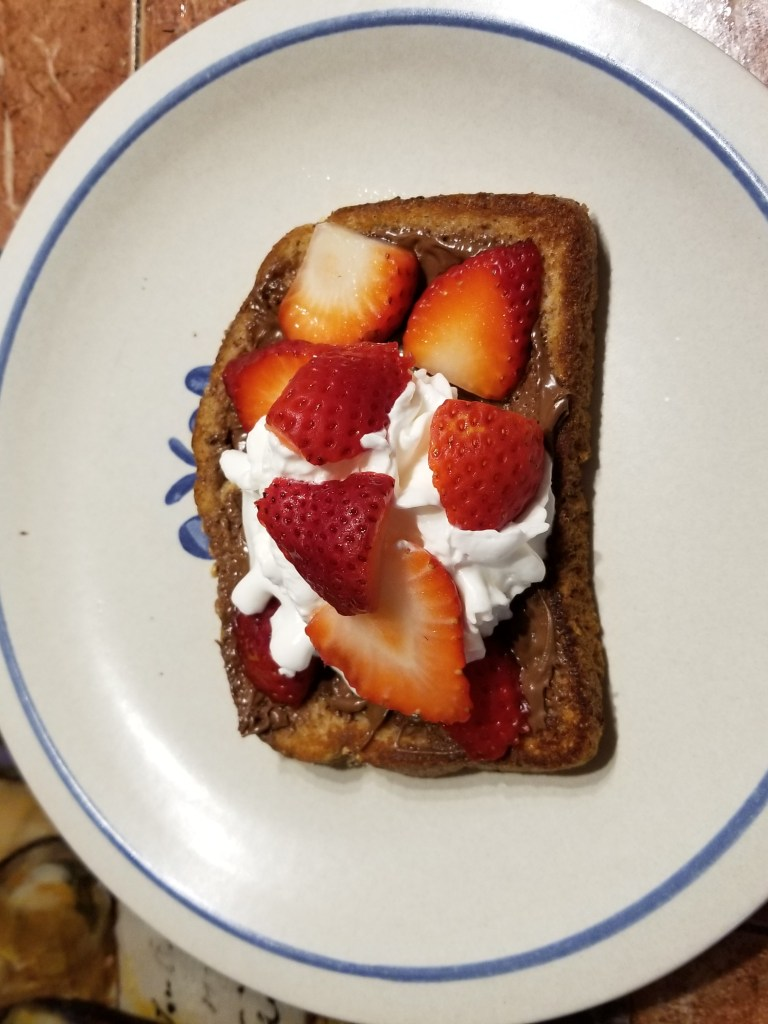 Valentine Day recipe for breakfast: shows french toast topped with nutella, whipped cream, and fresh strawberries