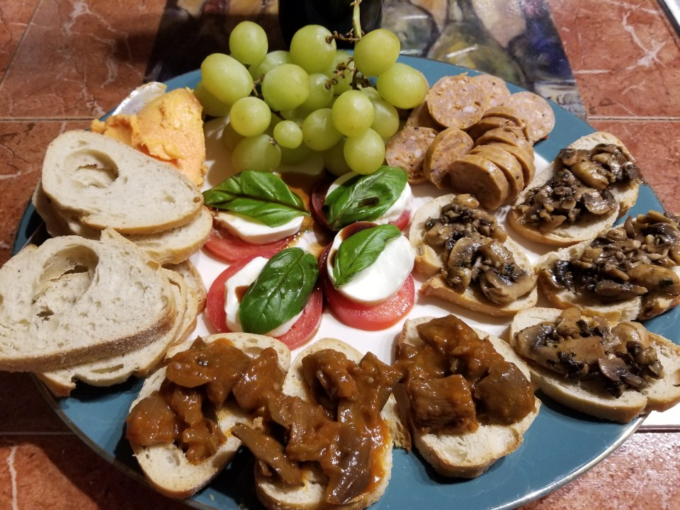 A cheese and meat board from Italy, with caprese, mushroom bruschetta, grapes, cheese, italian sausage and caponata