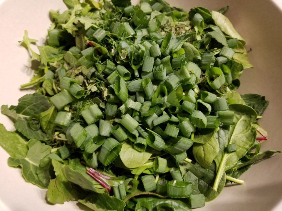 Spring green salad with chopped onions and dill as part of Easter dinner traditions in Greece
