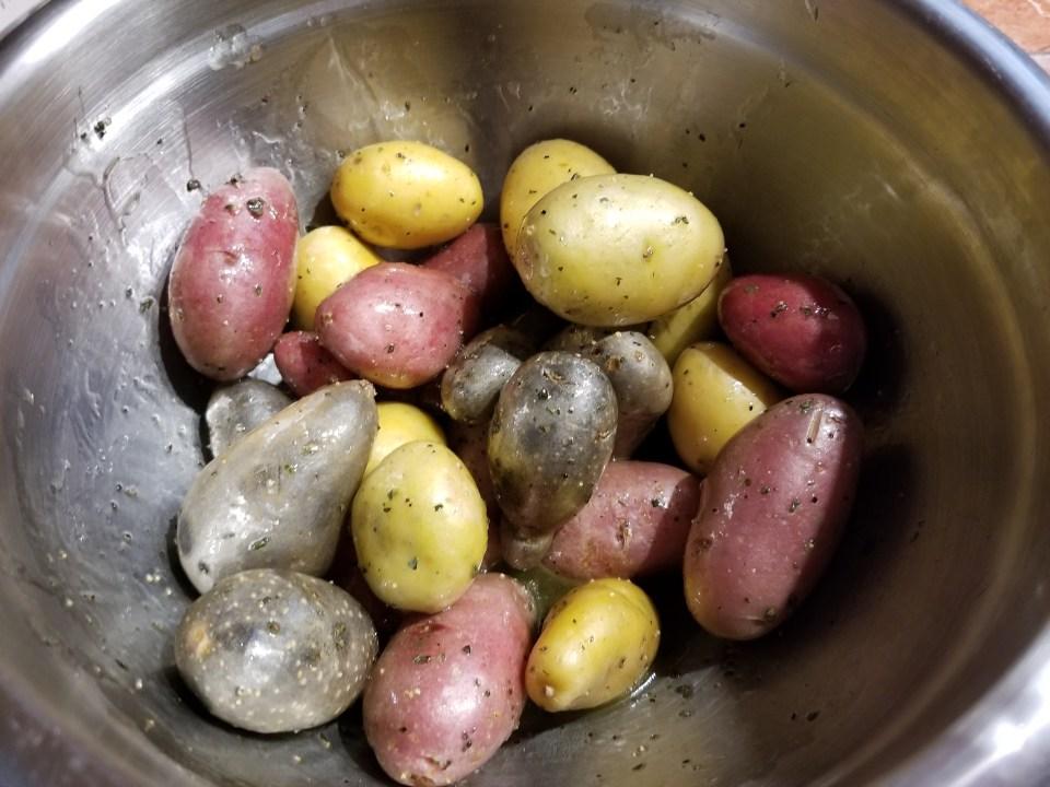 potatoes tossed in a bowl with lemon juice, oil, and seasonings