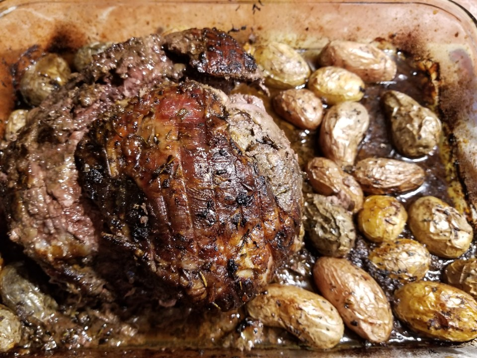 roasted leg of lamb with small roasted potatoes as part of Easter dinner traditions in Greece