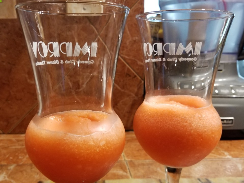 two glasses filled a third of the way with a frozen red drink as a first step to making red white and blue drinks