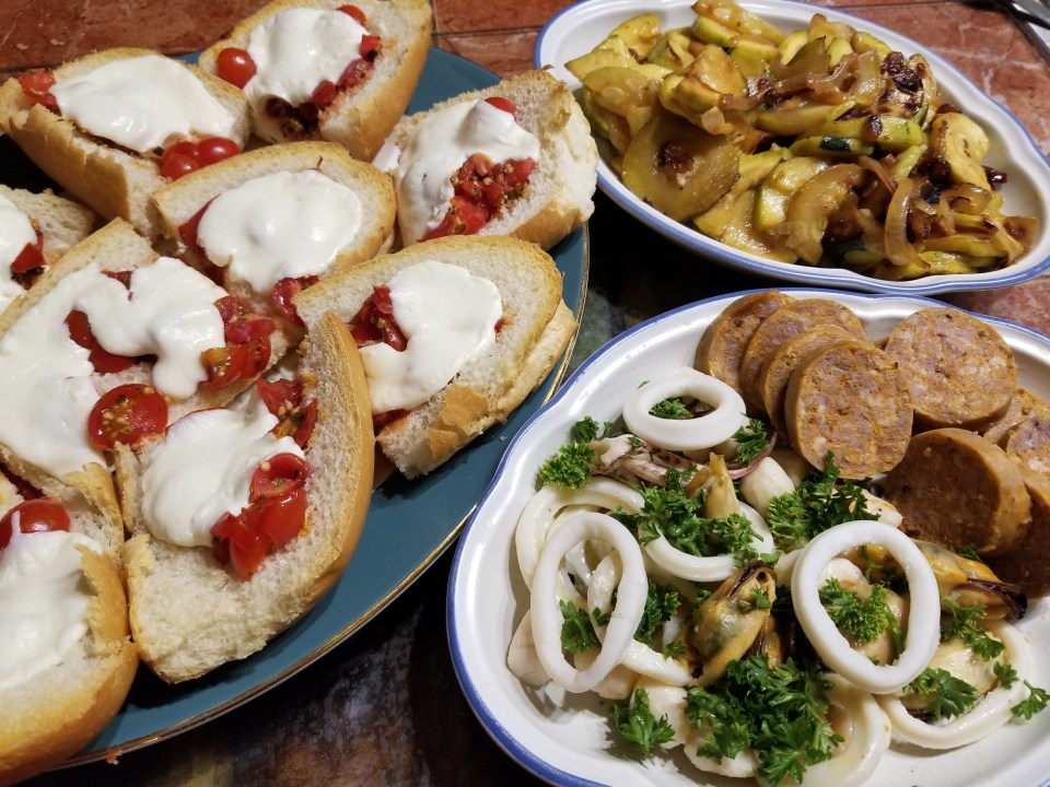 world foods from Italy: Italian grilled cheese, zucchini salad, sliced sausage, mixed seafood salad, served on a platter