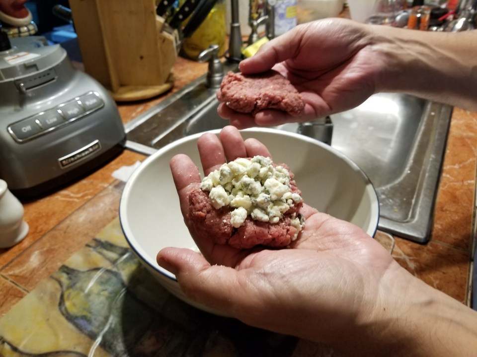 A half burger patty with blue cheese crumbles on top for black and blue best burgers recipe