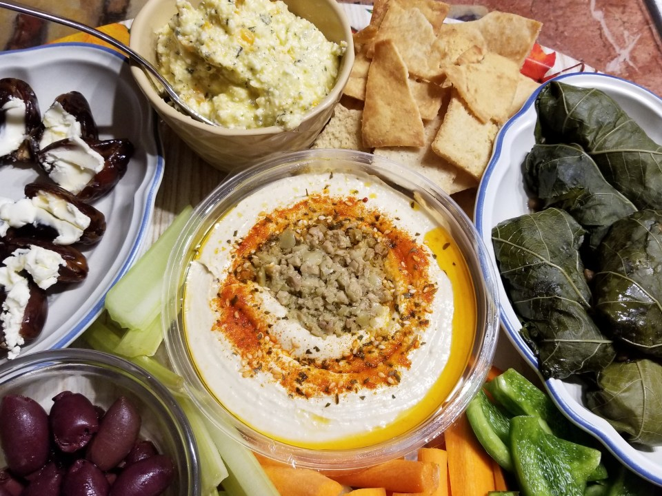 world food platter from the middle east: dates, Kalamata olives, hummus with raw vegetables, ricotta dip, pita chips, and stuffed grape leaves