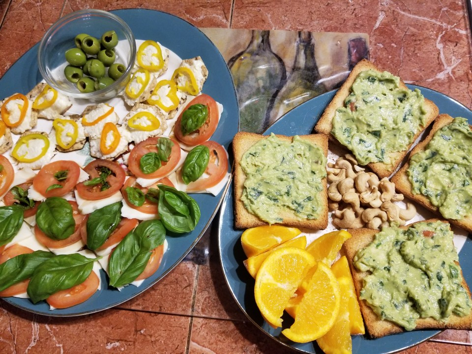 Eclectic platter: caprese, whole grain crackers with mini bell pepper rings, green olives, sliced oranges, cashews, and avocado toasts