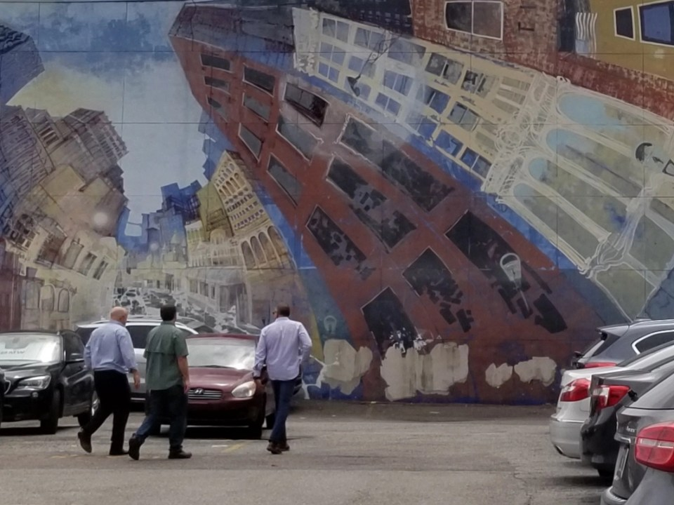 looking at street murals is one of the things to do in Jacksonville, FL This one shows building curving so that they look as if they are inside a globe.