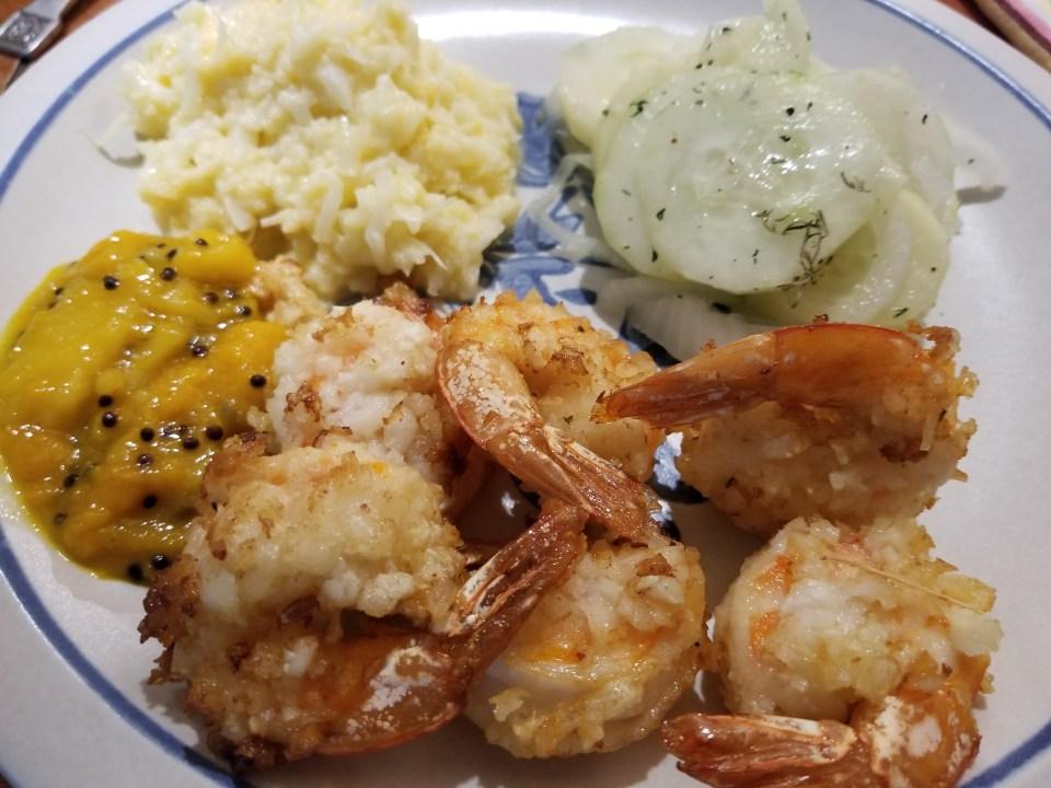 shows sauce for coconut shrimp, coconut shrimp and cucumber salad