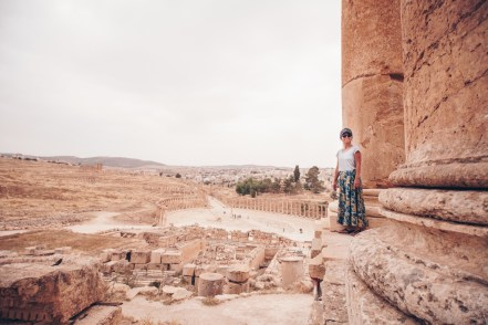 woman standing next to large pillars in Jerash