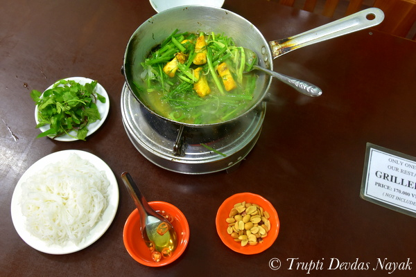 Cha Ca La Vong being cooked with dill herbs