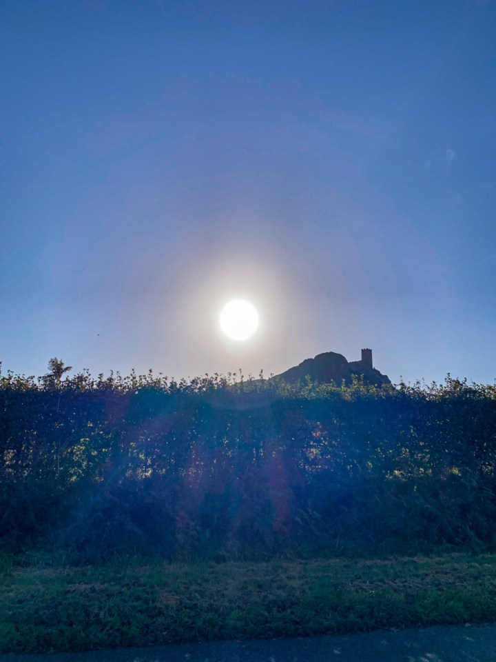Brentor Church and Brent Tor silhouetted against the sun