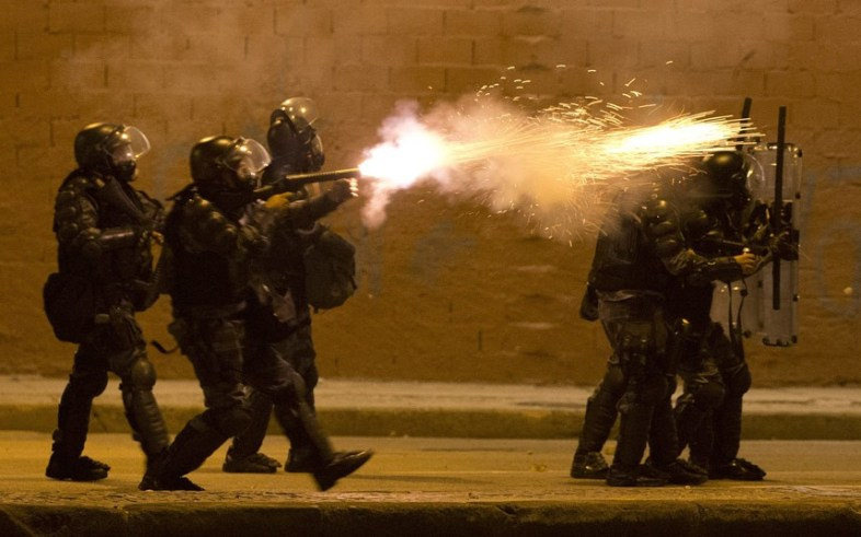 A military police officer fires tear gas at protestors during an anti-government demonstration in Rio de Janeiro