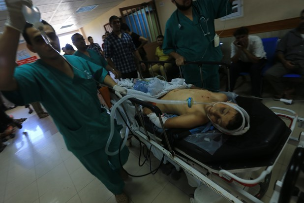 A Palestinian boy wounded by Israeli shelling receives treatment at al-Shifa hospital in Gaza City, 20 July.