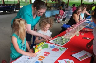 Adults help children make gardening posters.