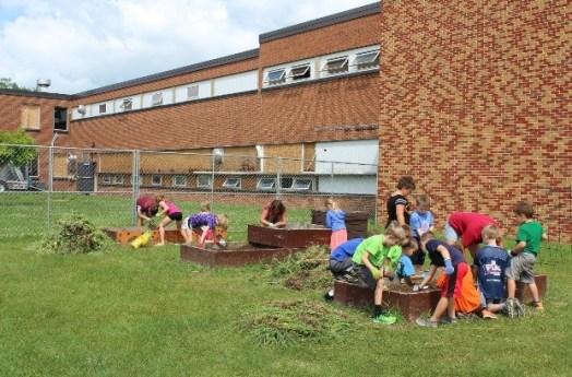 Children plant seeds in raised beds at Waukon school gardens.