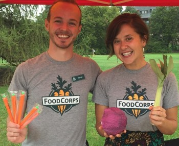 Smiling man and woman holding vegetable-shaped promo items.