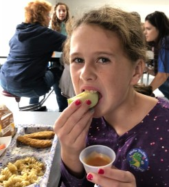 Girl eats apple slice at school lunch.