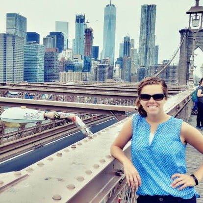Woman standing on Brooklyn Bridge with New York skyline behind her.