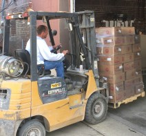 Man moving pallet of boxes with skid loader.