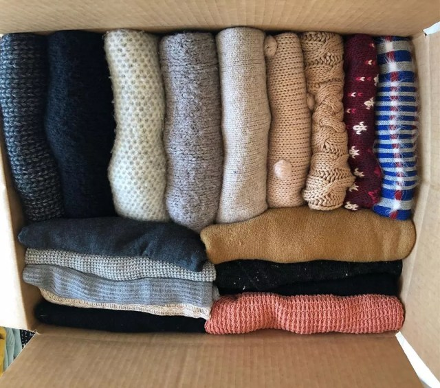 Sweaters neatly folded in large moving box. Photo by Instagram user @chaos.organizer