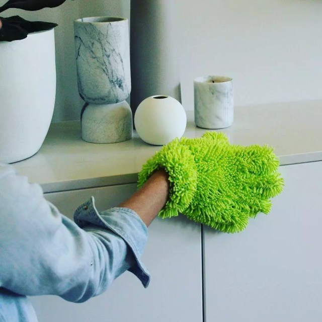 Hand wearing duster cleaning home. Photo by Instagram user @affordable_cleaning_supplies