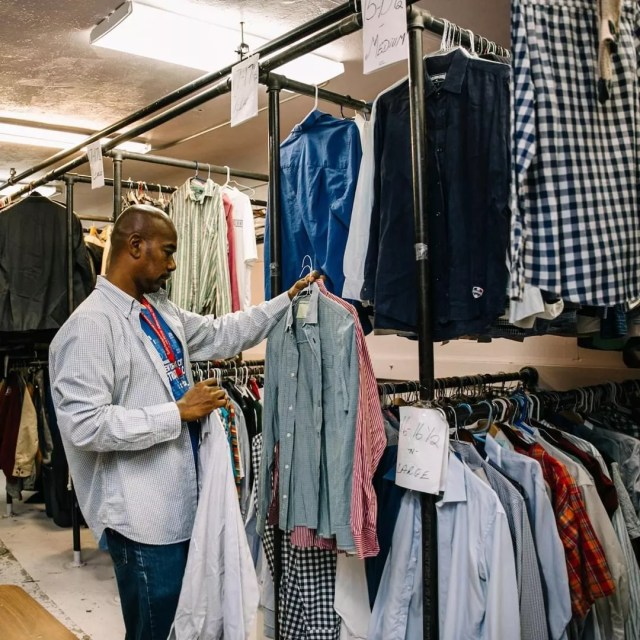 Man Looking Through Donated Clothes on Rack at The Bowery Mission. Photo by Instagram user @bowerymission