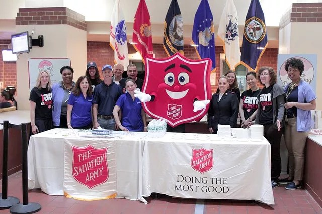 Volunteers and Mascot Behind a Table at a Booth for the Salvation Army. Photo by Instagram user @salvationarmyny