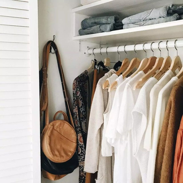 Closet filled with neutral-colored clothes and brown purse. Photo by Instagram user @caroline_joy