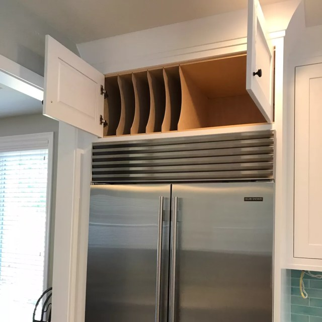 Space above the fridge with dividers for storage. Photo by Instagram user @hambuilt