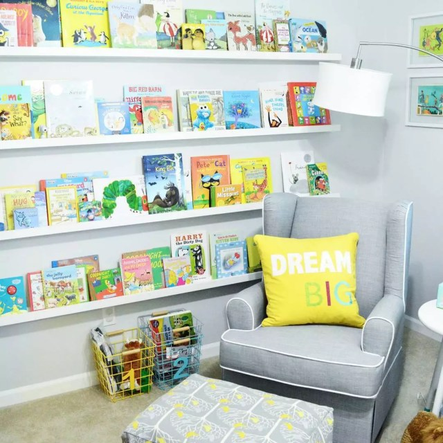 Nursery room with wall of books. Photo by Instagram user @lovinghereblog