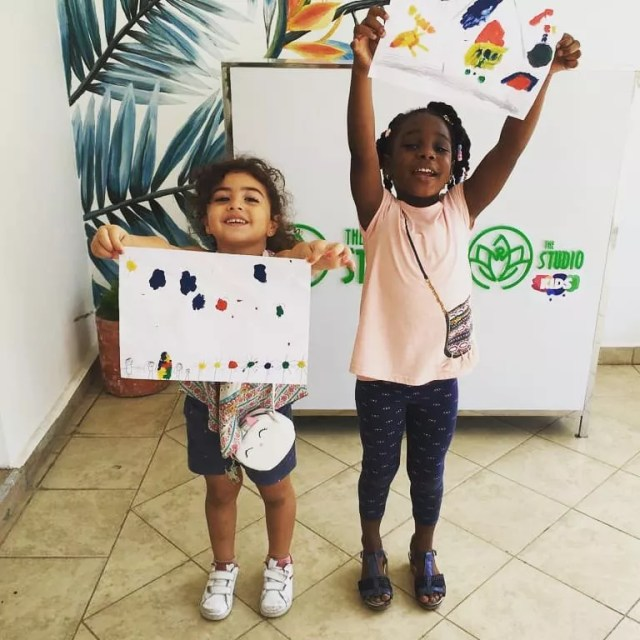 Little girls holding up paintings at The Studio. Photo by Instagram user @thestudiokids_online