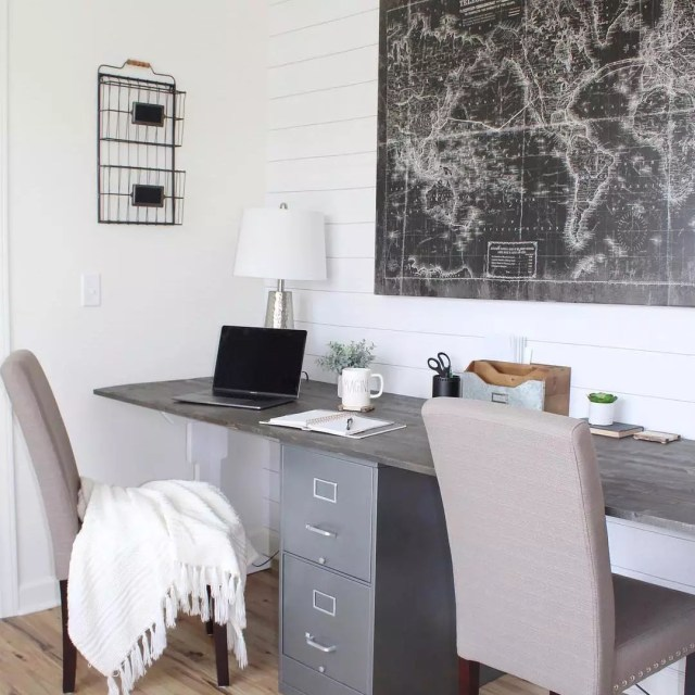 dark home desk with two chairs in front and map on the wall photo by Instagram user @theholtzhouse