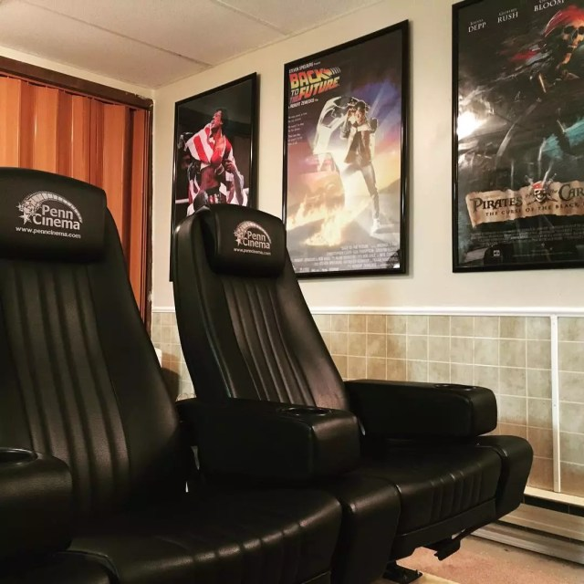 actual movie theater seats in home theater with movie posters on the wall photo by Instagram user @damianonair