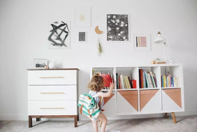Baby girl running over to storage dresser with books. Photo by Instagram user @ourlittleredhome