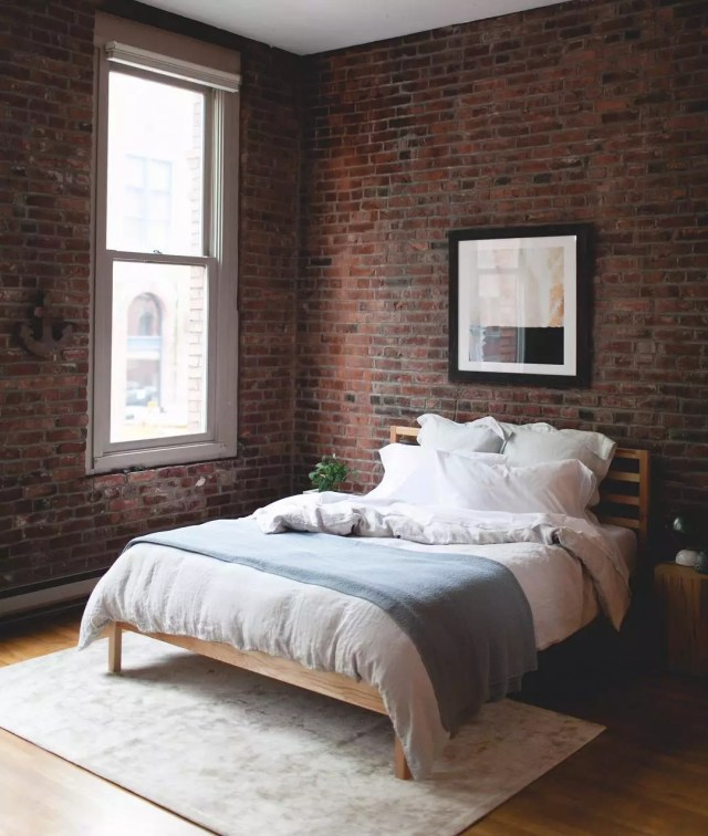 Bed with White Sheets in Brick Bedroom. Photo by Instagram user @jojotastic