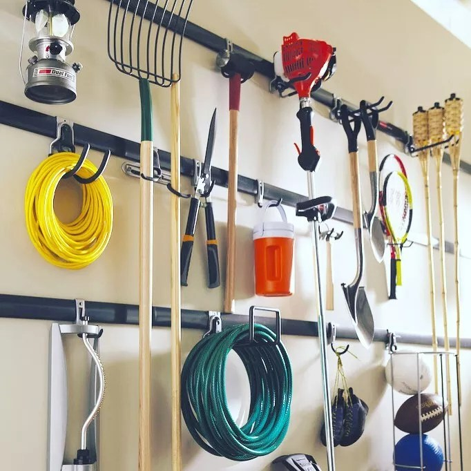 Gardening Tools and Hoses Hung on Garage Hooks. Photo by Instagram user @org_relo