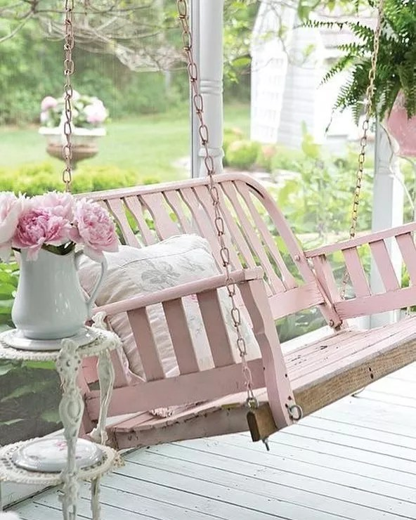 front porch with pink porch swing photo by Instagram user @pennyscallandesign