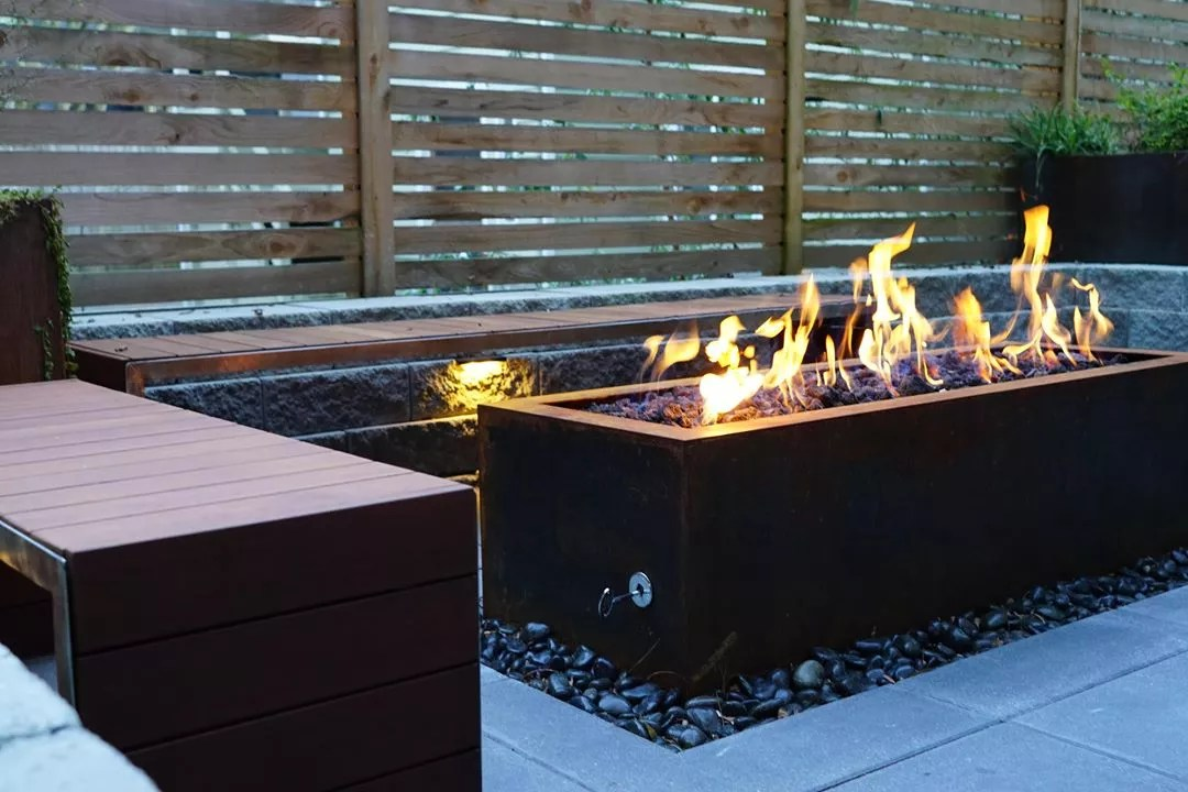 fire pit table in front of bench seating in backyard photo by Instagram user @truescapedesign