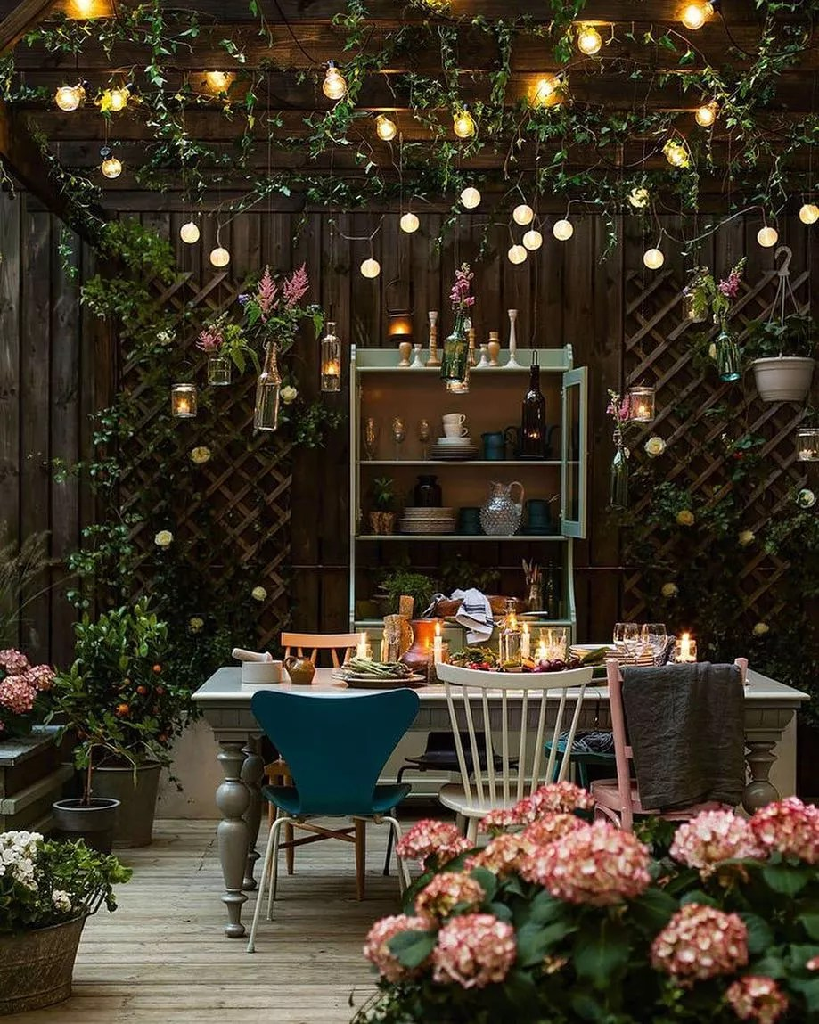 pergola over the top of a small backyard with vines and string lights hanging from it photo by Instagram user @travel.loverxo