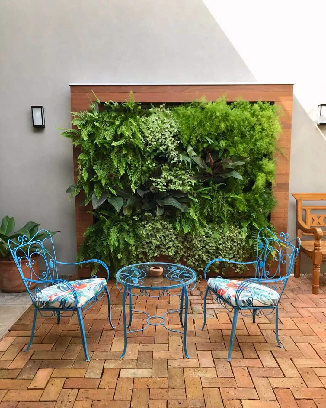 vertical garden wall behind a small bistro set of chairs and a table photo by Instagram user @nogueiraecamillo.arq