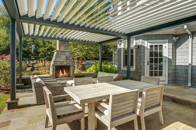 outdoor living space under pergola with fireplace added in photo by Instagram user @paula_sells_victoria