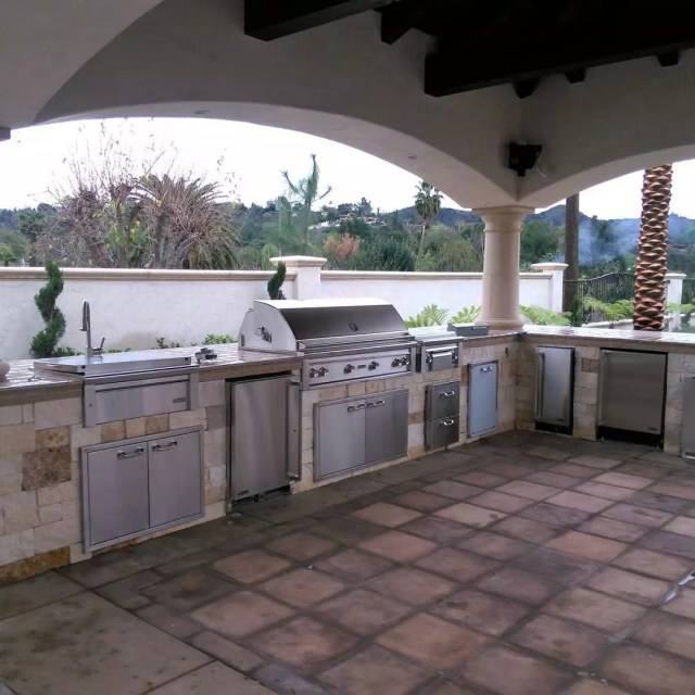 outdoor kitchen built using tile counters next to grill and sink photo by Instagram user @johnnysconcrete
