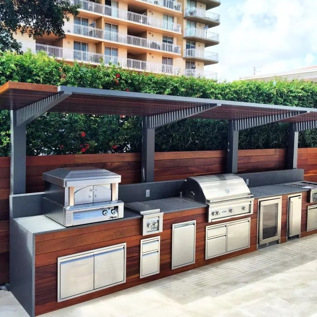 modular outdoor kitchen area built with grill, stove burners, pizza over, and fridge photo by Instagram user @luxapatio
