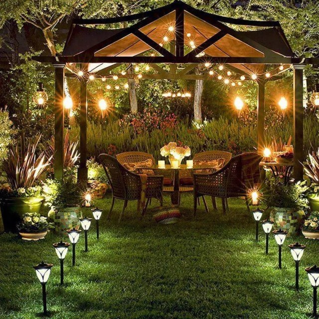 small dining set under a pergola with garden lighting leading to seats in grass photo by Instagram user @have2havehome