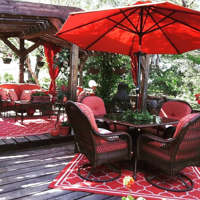 back deck with multiple seating areas and an umbrella photo by Instagram user @debradolechek