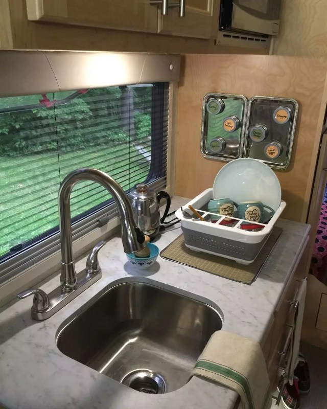 Small RV kitchen with dish organizer. Photo by Instagram user @girl_camper