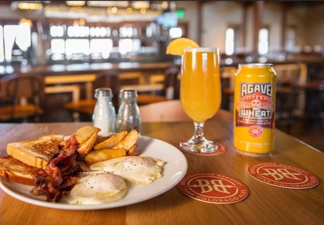 Plate of eggs, toast, bacon and potato wedges on a table alongside a glass of beer and a can Photo by Instagram user @breckbrewfarmhouse