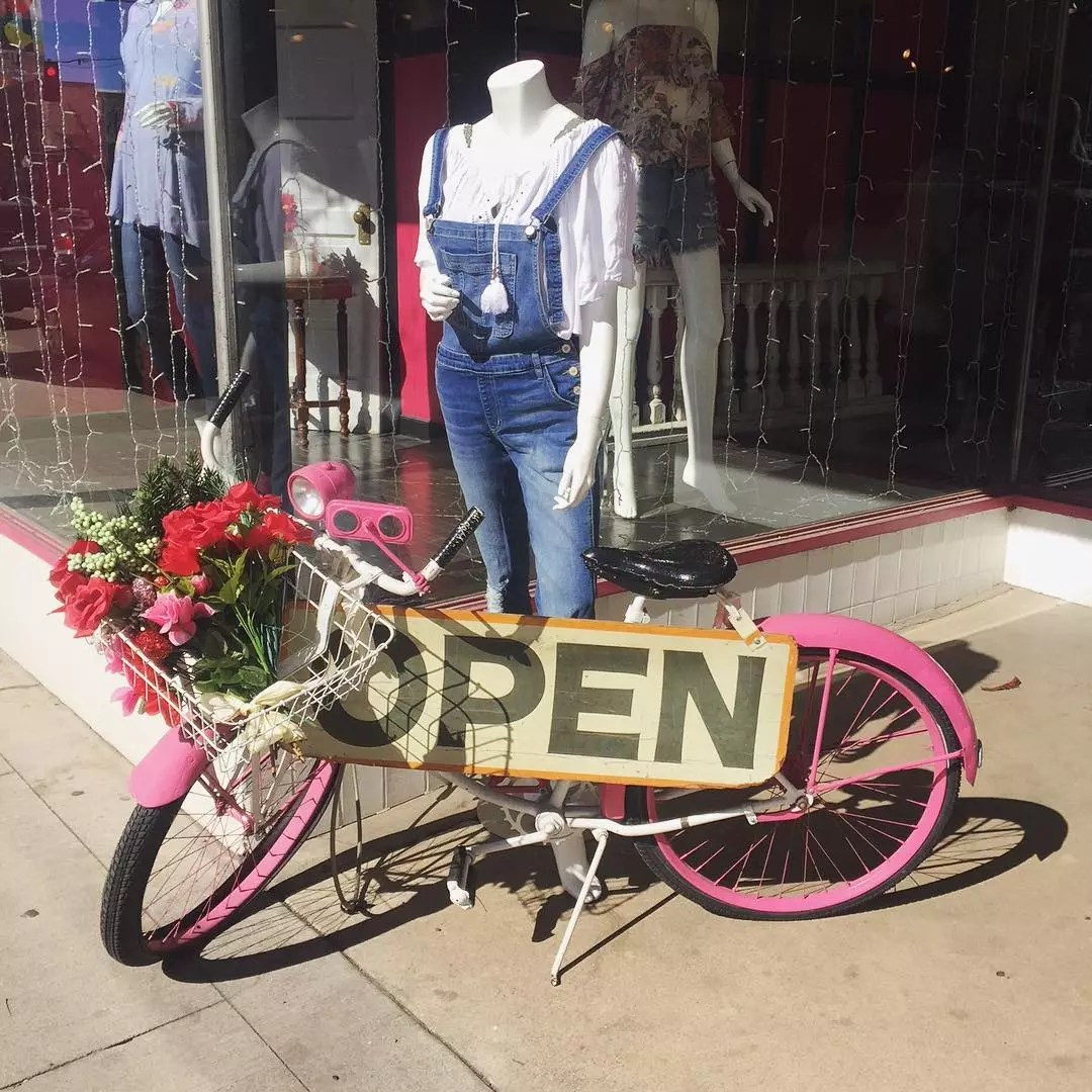 Front of boutique with mannequin and pink bicycle in front with an open sign Photo by Instagram user @detailsboutique