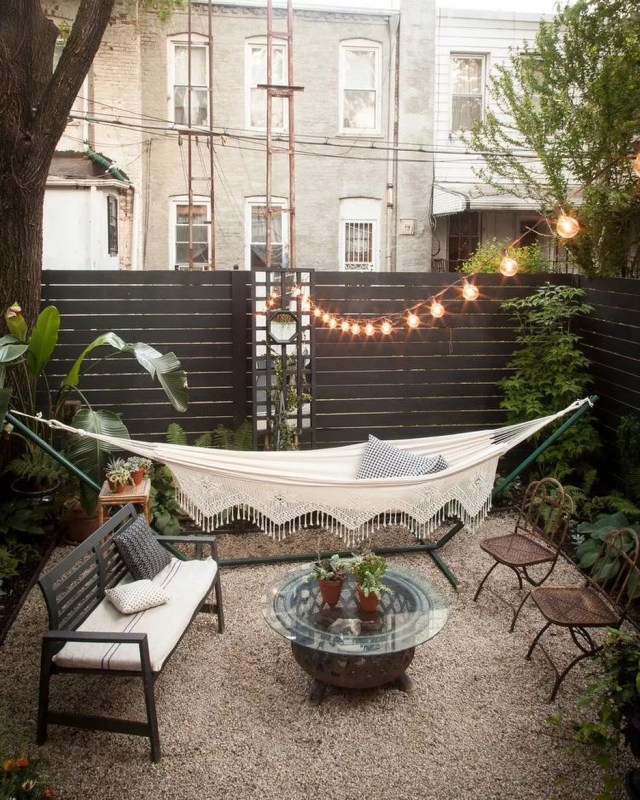 hammock strung up in backyard under string lights photo by Instagram user @thefarrisgroup